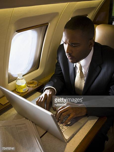 Businessman working on a laptop in an airplane