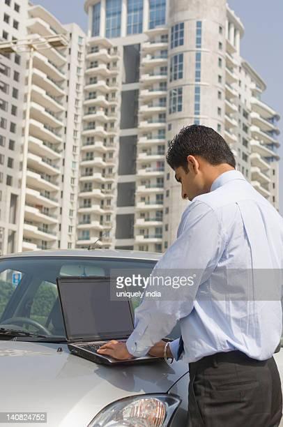 Businessman working on a laptop on a car hood, Gurgaon, Haryana, India
