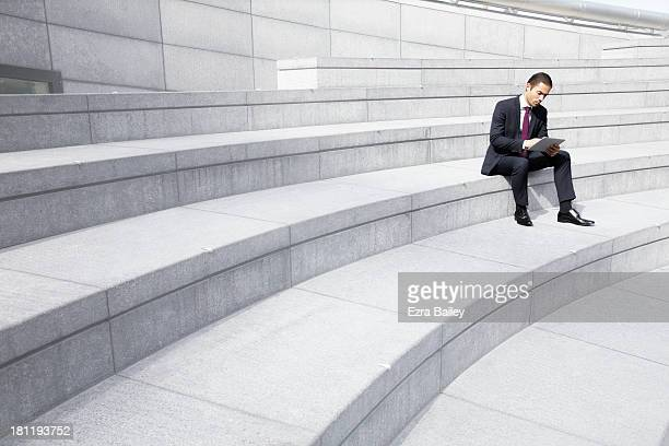 Businessman working on a tablet outside.