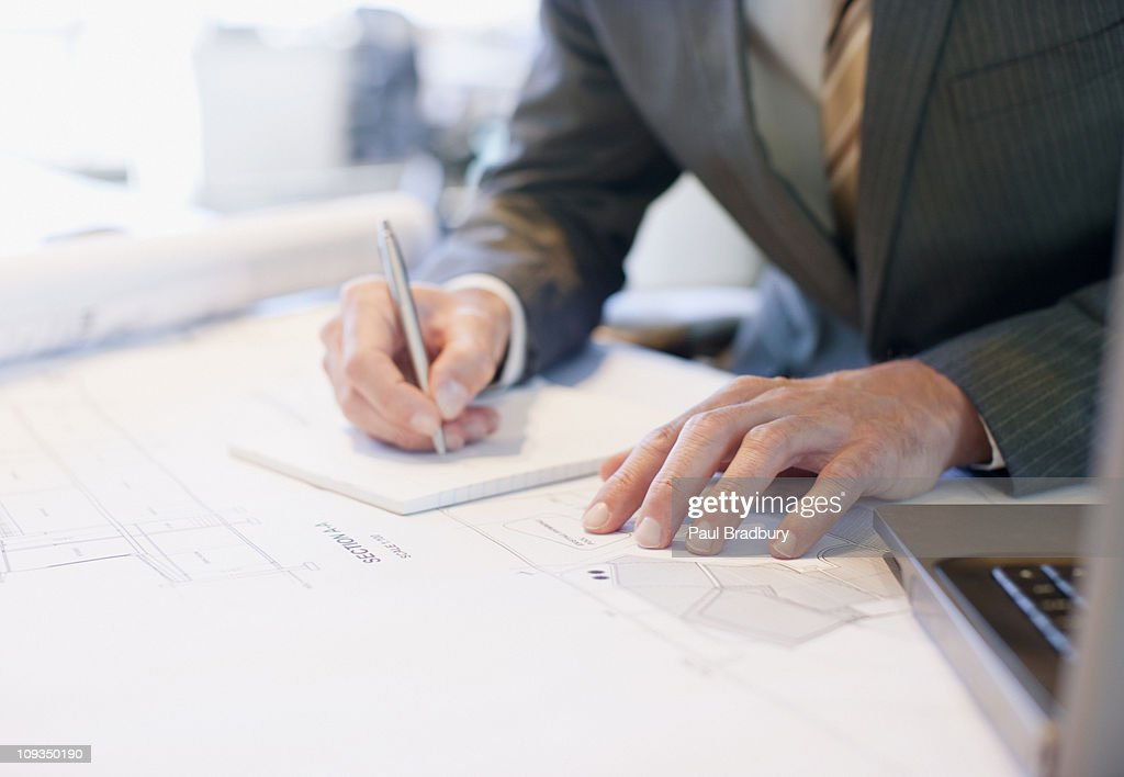 Businessman working on blueprints in office : Stock Photo