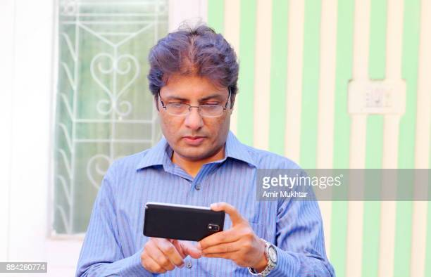 businessman working on cell phone - amir mukhtar stock photos and pictures