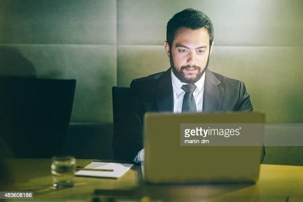 Uomo d'affari che lavorano su computer dopo l'orario di