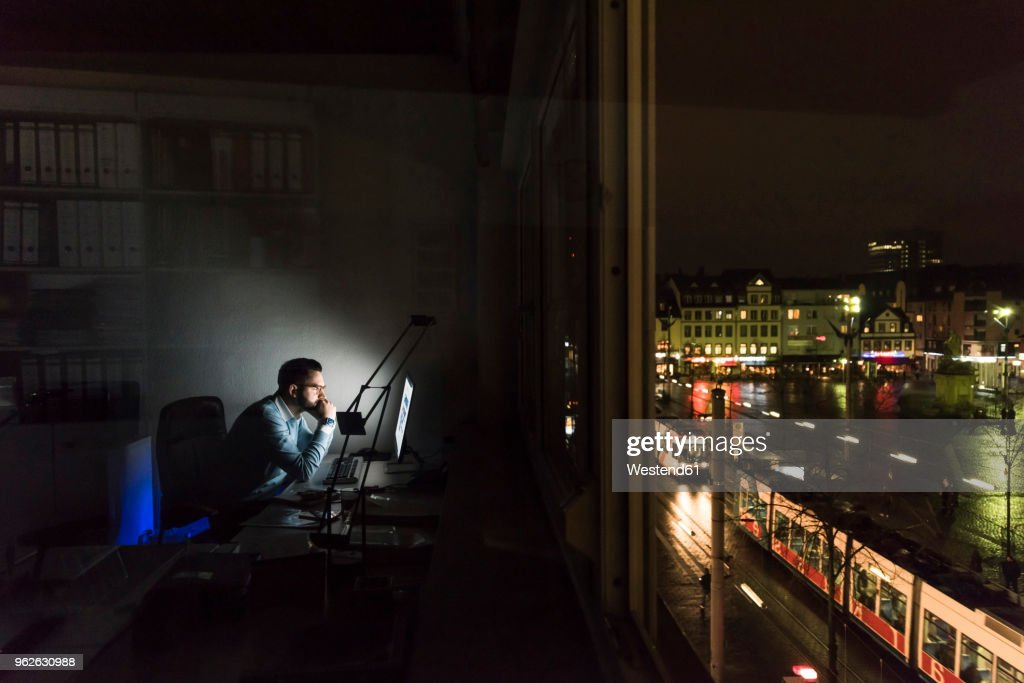 Businessman working on computer in office at night : Stock-Foto