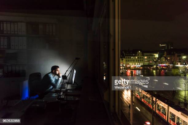 businessman working on computer in office at night - noche fotografías e imágenes de stock