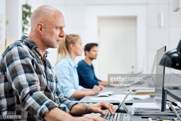 businessman working on computer with coworkers - concentration stock pictures, royalty-free photos & images