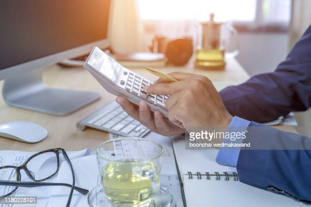 businessman working on desk office with using a calculator to calculate the numbers, finance accounting concept - stock certificate stock pictures, royalty-free photos & images