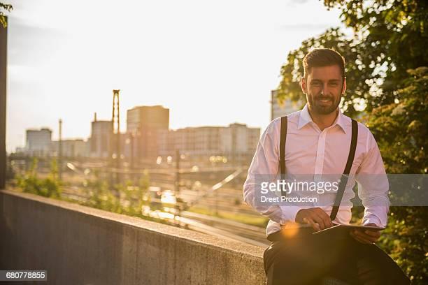 Businessman working on digital tablet at sunset, Munich, Bavaria, Germany