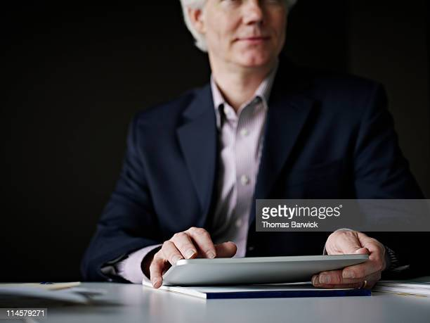 Businessman working on digital tablet smiling