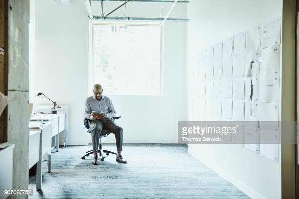 Businessman working on digital tablet while reviewing plans on office wall