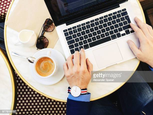 businessman working on his laptop and drinking coffee at the cafe, personal perspective view - e mail foto e immagini stock