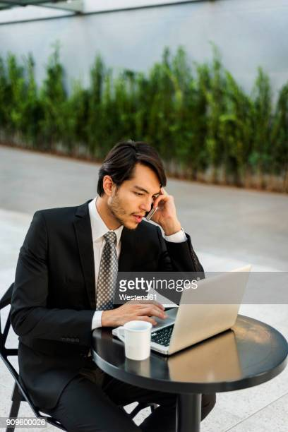 Businessman working on laptop and talking on cell phone outdoors