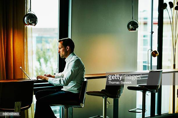 Businessman working on laptop at counter in office