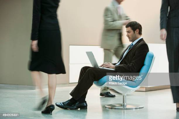 Businessman working on laptop in busy lobby area