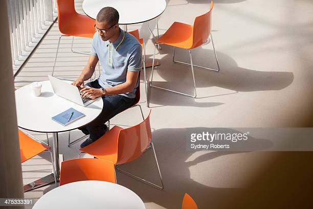 businessman working on laptop in cafe - oranje stockfoto's en -beelden
