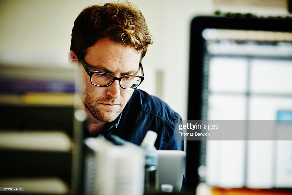 Businessman working on laptop in startup office : Stock Photo