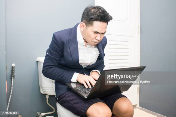Businessman Working On Laptop In Toilet