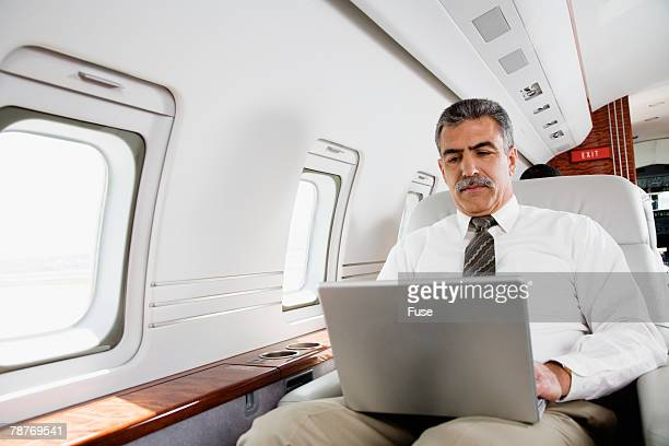 Businessman Working on Laptop on Private Jet