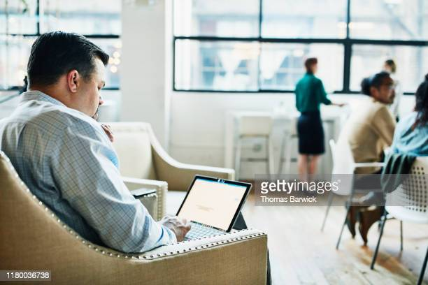 businessman working on laptop while working in coworking office - incidental people stock pictures, royalty-free photos & images
