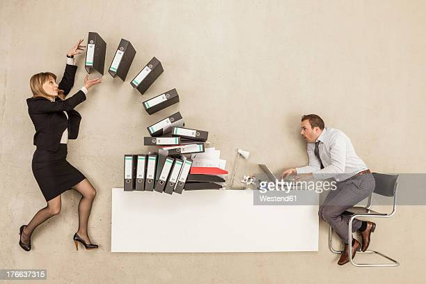 Businessman working on office desk while businesswoman providing stack of files