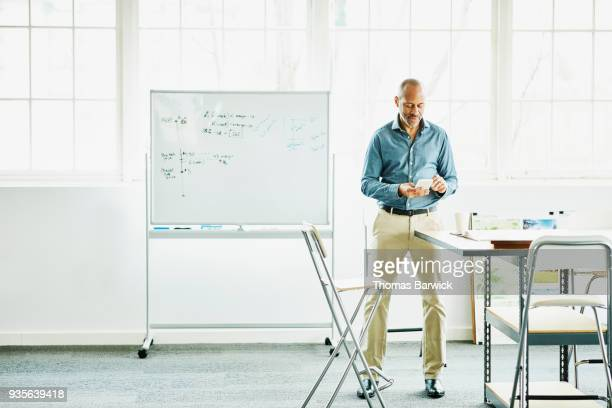 businessman working on smartphone in design studio - cream colored shoe stock pictures, royalty-free photos & images