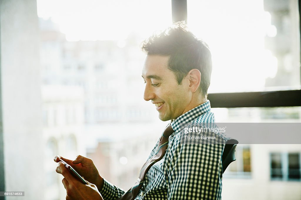 Businessman working on smartphone in office : Stock-Foto
