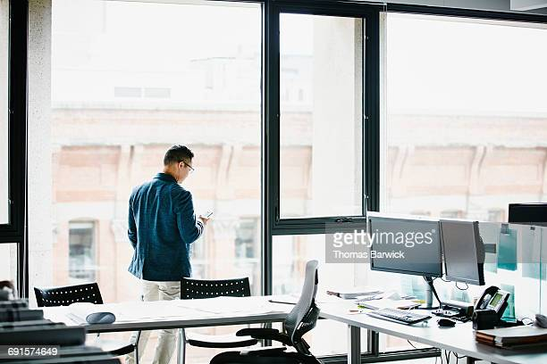 businessman working on smartphone in office - world at your fingertips stock pictures, royalty-free photos & images