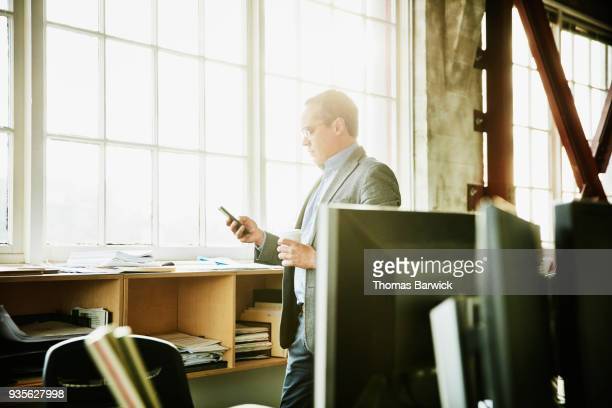 Businessman working on smartphone while standing in design office
