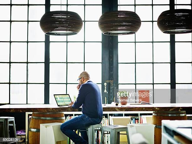 Businessman working on spreadsheet on laptop
