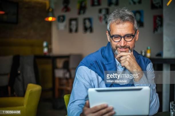 empresario que trabaja en la tableta - 55 59 años fotografías e imágenes de stock