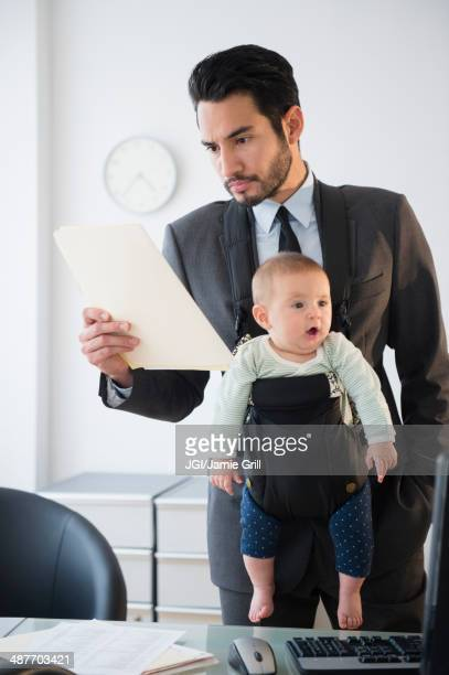 Businessman working with baby in office