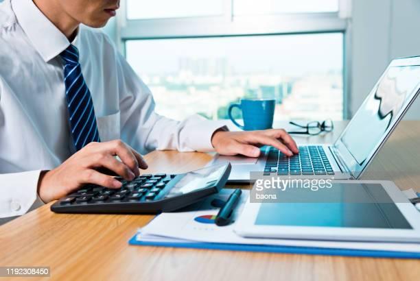 geschäftsmann arbeitet mit digitalem tablet und laptop im büroraum - rechnungswesen stock-fotos und bilder