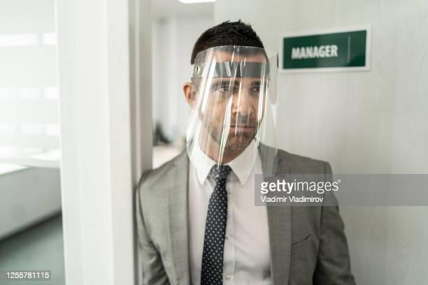 covid-19パンデミック中にオフィスでフェイスシールドを扱うビジネスマン - フェイスシールド ストックフォトと画像