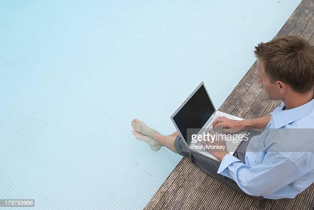 Hombre de negocios trabajando con los pies en la piscina