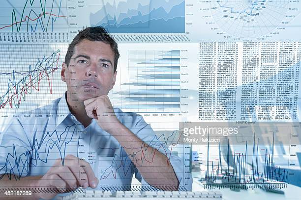 Businessman working with graphs and charts seen through screen