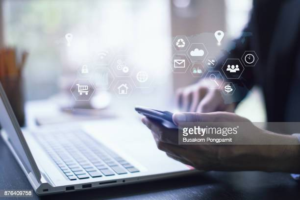 businessman working with laptop computer and digital tablet and smart phone in modern office with virtual icons interface - marketing icons stock photos and pictures