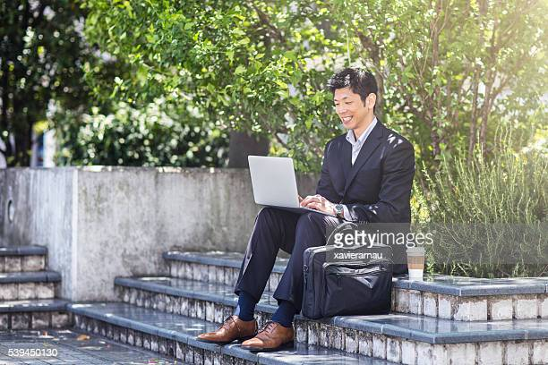 Businessman working with laptop on building steps