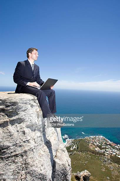Businessman working with laptop on seaside cliff