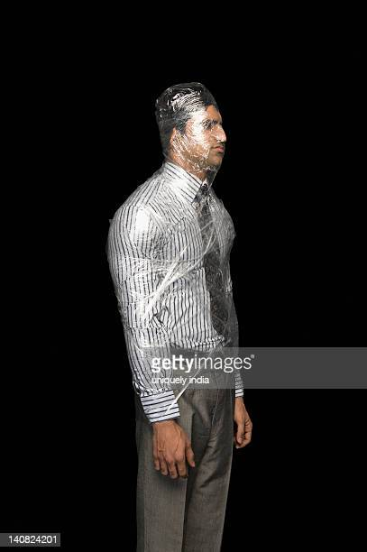 Businessman wrapped in a plastic wrap