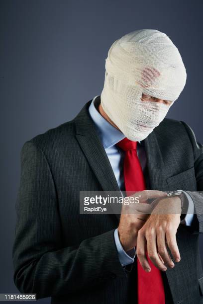businessman wrapped in bandages checks the time on his watch - cut wrists stock photos and pictures