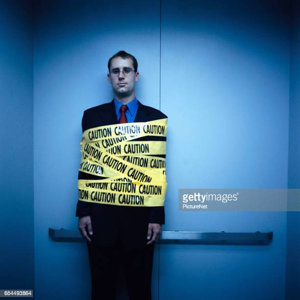 Businessman Wrapped in Caution Tape
