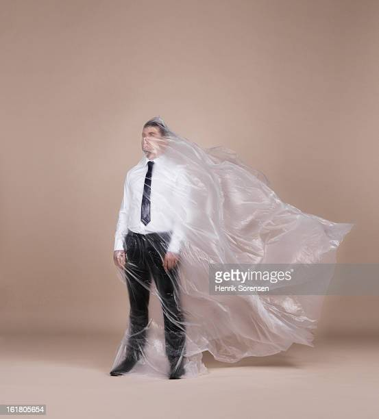 businessman wrapped in plastic - man wrapped in plastic stock pictures, royalty-free photos & images
