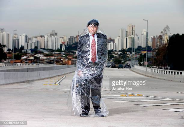 businessman wrapped in polythene standing on road - man wrapped in plastic stock pictures, royalty-free photos & images