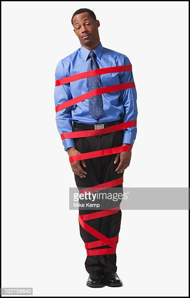 businessman wrapped in red tape - eingewickelt stock-fotos und bilder