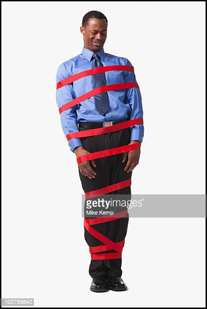 businessman wrapped in red tape - the black tape project stock-fotos und bilder