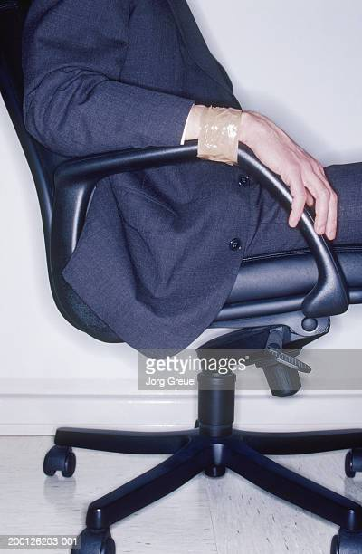 businessman, wrists taped to arms of chair, side view, mid section - man tied to chair stock photos and pictures