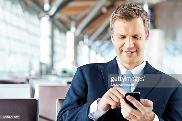 Businessman Writing a Text Message on His Phone At Airport