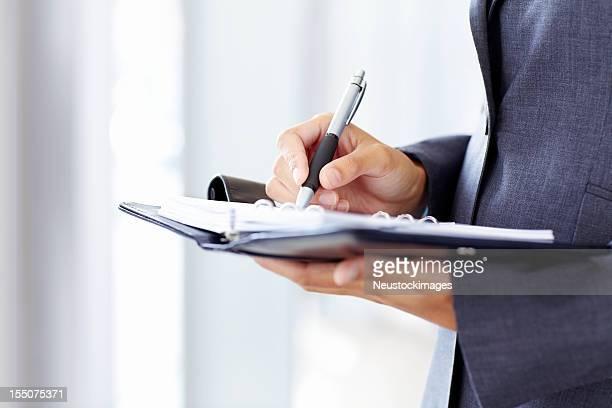 Geschäftsmann Schreiben in einem Planner