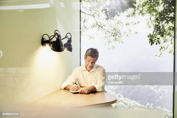 businessman writing in book at table in modern office with panorama window - non urban scene stock pictures, royalty-free photos & images
