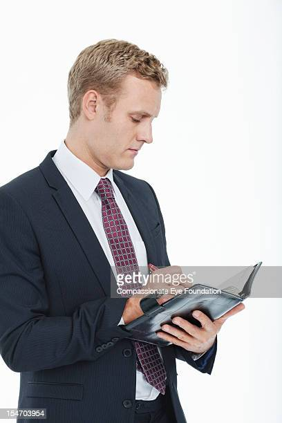 "businessman writing in diary - ""compassionate eye"" stock pictures, royalty-free photos & images"