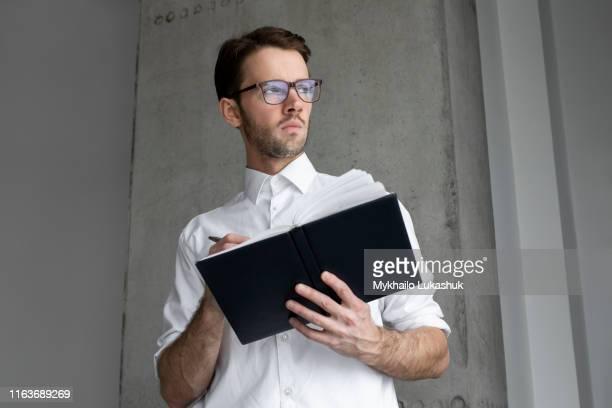 businessman writing in note book - 袖を折った袖まくり ストックフォトと画像